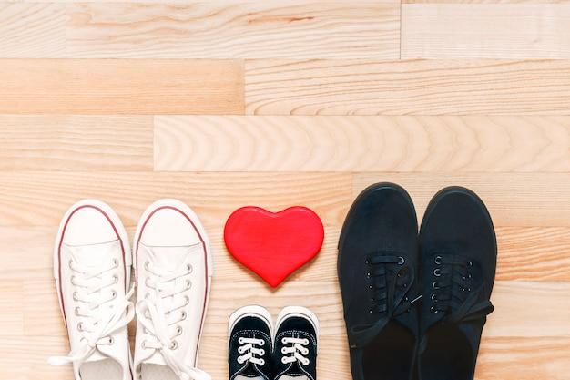 Concetto di famiglia felice. scarpe padre, madre e bambino sul pavimento di legno con cuore rosso. simbolo di crescita familiare, divertimento, amore, solidarietà, calore e cura. vista dall'alto. spazio per il testo