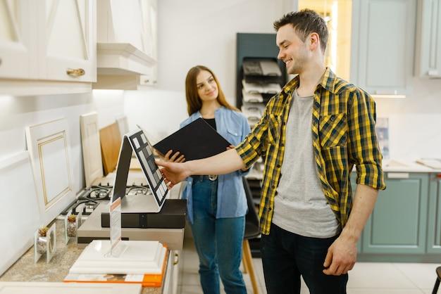 Coppia felice della famiglia nel negozio di mobili. uomo e donna che guardano il piano del tavolo in negozio, marito e moglie acquistano beni per interni domestici moderni