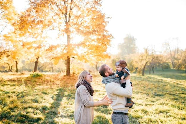 La coppia felice della famiglia abbraccia il loro bambino adorabile nel parco soleggiato di autunno
