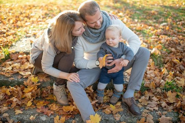 Coppie felici della famiglia che si siedono sulle scale coperte dalle foglie di autunno e che tengono il loro bello bambino.