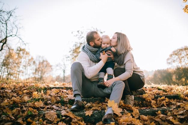 Coppie felici della famiglia che si siedono sulle scale coperte dalle foglie di autunno e che baciano il loro bello bambino.