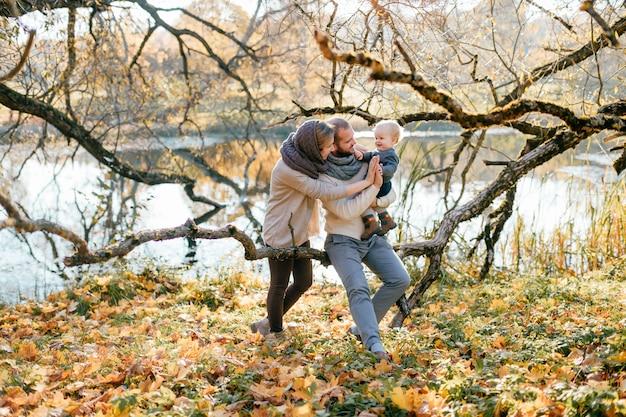 Le coppie felici della famiglia con il loro piccolo bambino in autunno parcheggiano nel giorno soleggiato