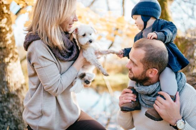 Le coppie felici della famiglia con il loro piccolo bambino e cucciolo che spendono il tempo in autunno parcheggiano.