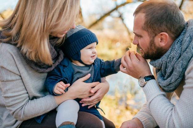 Coppia famiglia felice con il loro bambino piccolo trascorrere del tempo all'aperto.