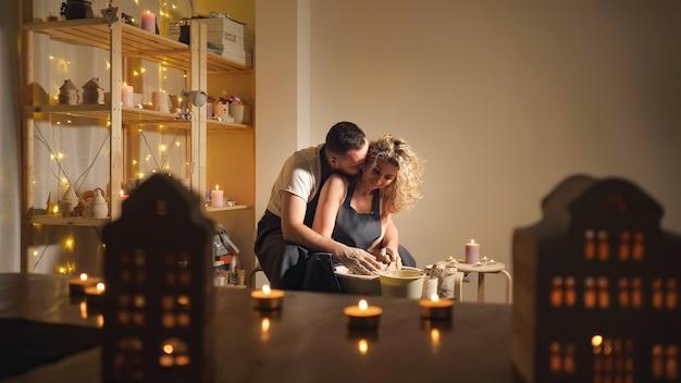 Famiglia felice in una vacanza congiunta creativa. uomo barbuto e una giovane donna modellano un vaso in un laboratorio artigianale.