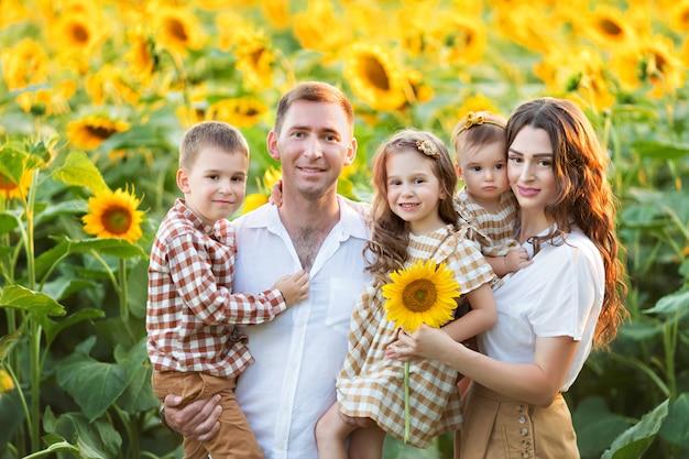 Famiglia felice, papà, figlia e figlio si divertono, giocano tra i girasoli in fiore all'aria aperta