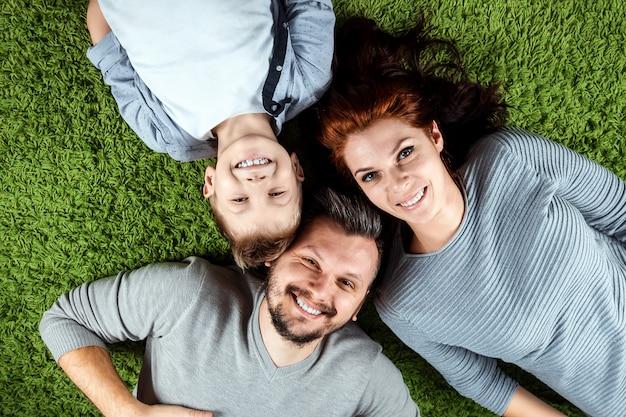 Famiglia felice, papà mamma e figlio sorridono sdraiati su un tappeto verde