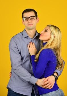 Buona giornata in famiglia. coppia innamorata. uomo e donna si abbracciano. ragazzo dall'aspetto intelligente indossa gli occhiali. ragazza sexy bonde abbraccia il suo ragazzo. concetto di relazione romantica. amore e appuntamento. buon san valentino.