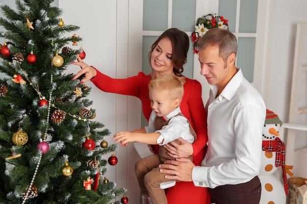 Famiglia felice che decora l'albero di natale. felice anno nuovo concetto
