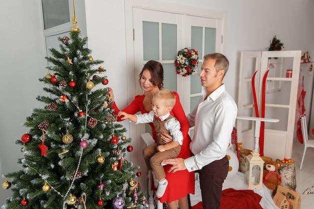 Famiglia felice che decora l'albero di natale vacanze e divertimento di capodanno