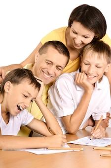 Famiglia felice che disegna insieme a tavola