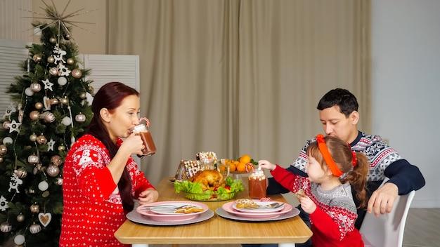 La famiglia felice beve bevande seduti a una cena festiva