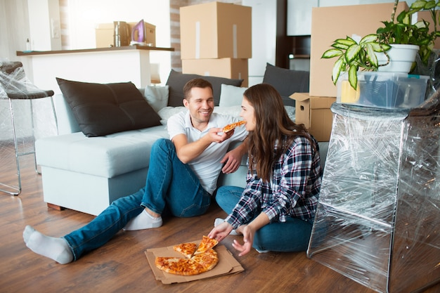 Famiglia felice che mangia pizza il giorno commovente. maschera di giovane coppia che gode del tempo di riposo mentre sedendosi insieme nella nuova casa.