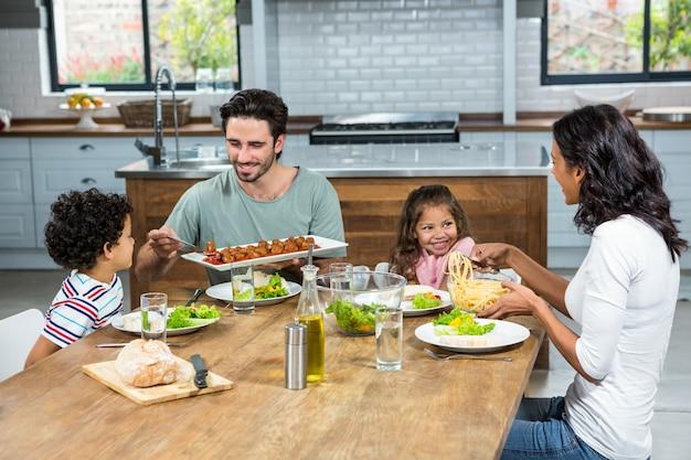 Famiglia felice che mangia insieme nella cucina