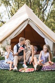 Famiglia felice che mangia anguria al picnic in prato vicino alla tenda di tipi di wigwam