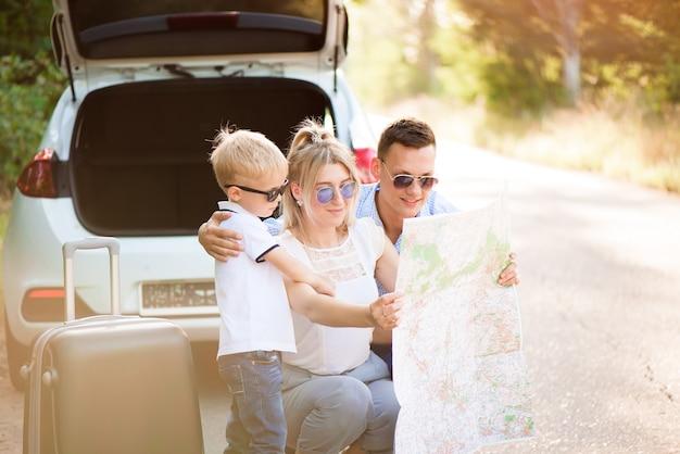 La famiglia felice gode del viaggio in macchina e delle vacanze estive.