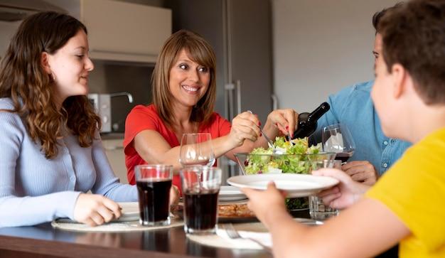 Famiglia felice che si gode il pranzo insieme a casa