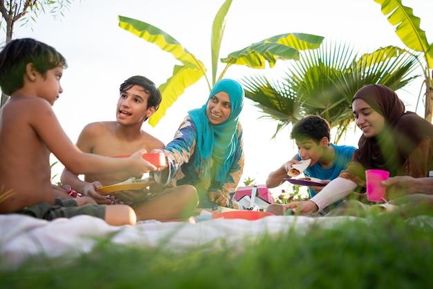Famiglia felice che gode del picnic sulla spiaggia vicino al mare