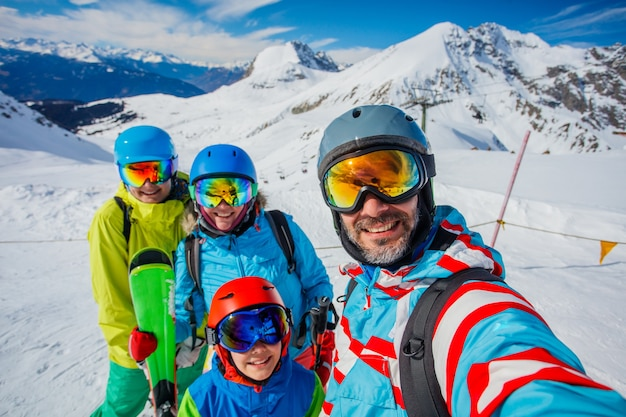 Famiglia felice che gode delle vacanze invernali in montagna