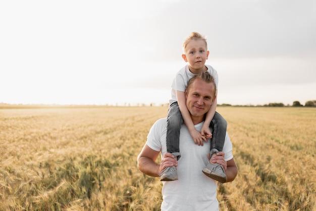 La famiglia felice di padre e figlio cammina su un campo di grano.