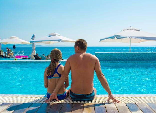 Famiglia felice. padre e figlia che godono dell'ora legale in piscina in una giornata di sole.