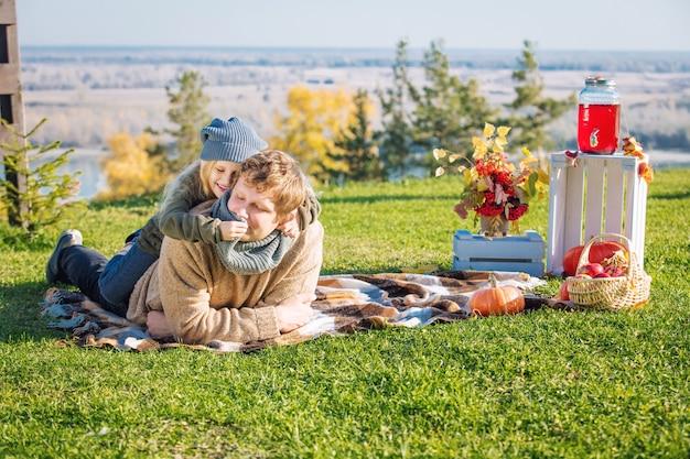 Felice padre e figlia di famiglia insieme nella natura durante un picnic con zucche a quadri