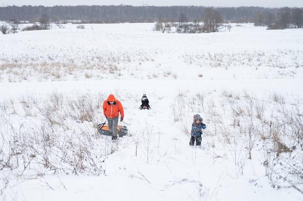 Felice famiglia, padre e figli, figlio e figlia, trascorrono le loro vacanze invernali innevate divertendosi e pedalando lungo gli scivoli nella natura all'aperto