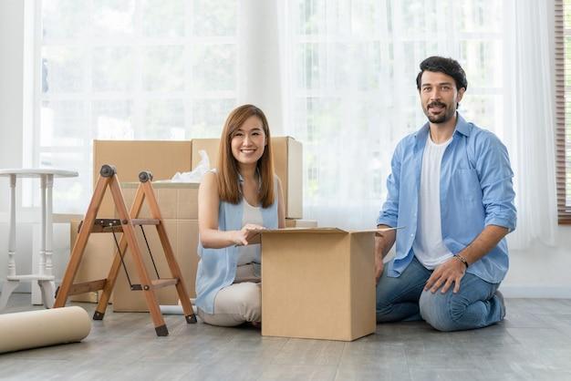 Padre e madre di famiglia felici che guardano la loro figlia mentre sono seduti a fare i bagagli in una scatola di cartone per trasferirsi in una nuova casa