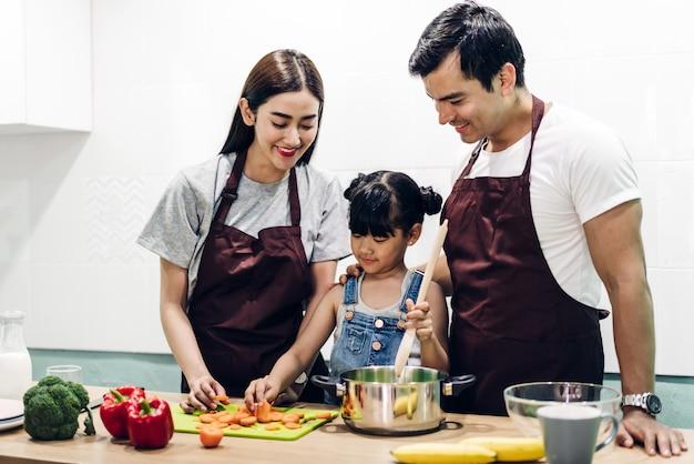 Padre e madre felici della famiglia con la figlia che cucina e che prepara insieme pasto nella cucina