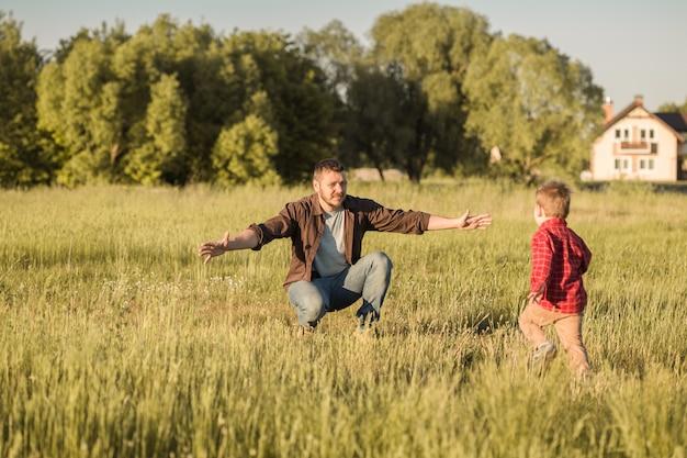 Famiglia felice. padre e figlio che giocano e abbracciano la vita all'aria aperta. festa del papà