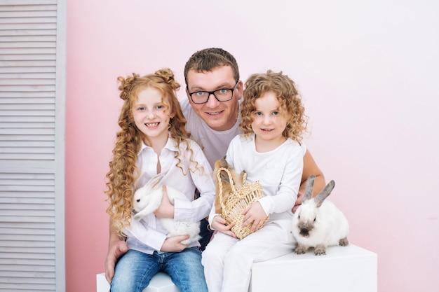 Padre di famiglia felice due figlie e animali soffici bellissimi conigli con sorrisi