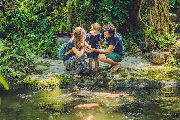 Famiglia felice che alimenta il pesce gatto variopinto nello stagno tropicale