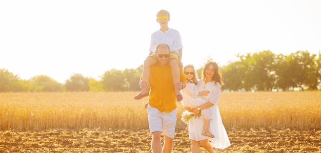 Felice famiglia di quattro persone stanno trascorrendo del tempo insieme alla luce del sole su un campo di grano.