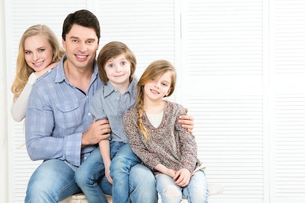 Felice famiglia di quattro persone che si legano a vicenda e sorridono a casa.