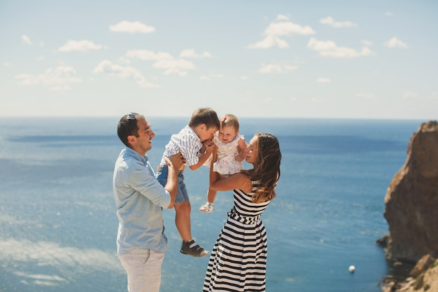 Felice famiglia di quattro persone che camminano in montagna. fratello e sorella che si baciano.