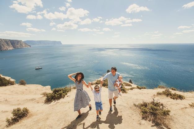 Felice famiglia di quattro persone che camminano in montagna. concetto di famiglia. viaggio in famiglia.