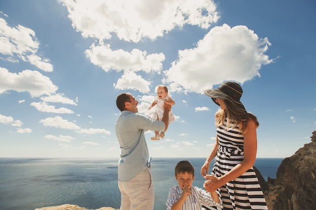 Felice famiglia di quattro persone che camminano in montagna. il padre lancia la figlia nel cielo.