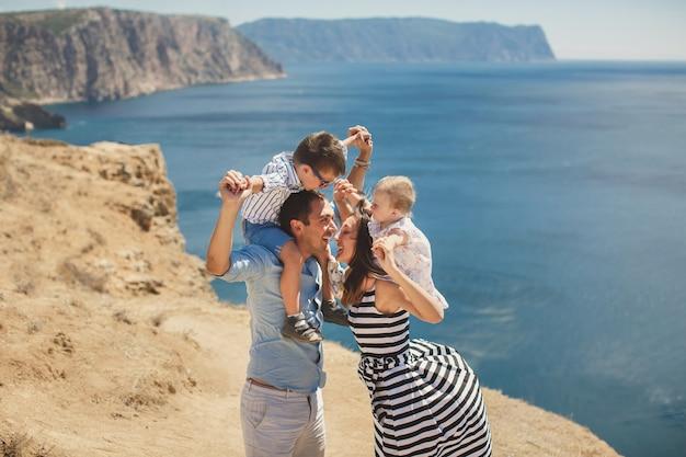 Felice famiglia di quattro persone che camminano in montagna. bacio.