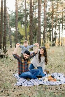 Famiglia felice, bel padre, madre attraente e gioioso figlio del bambino piccolo bambino, divertirsi insieme nella foresta di autunno, seduti su una coperta con frutti
