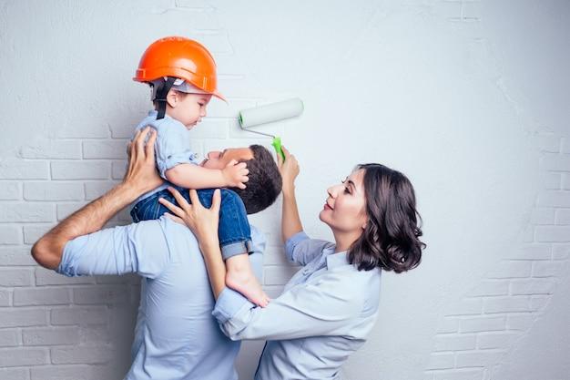 Un bell'uomo di famiglia felice e una donna affascinante e il loro piccolo figlio carino con un elmetto da elmetto dipinto con una parete di colore bianco della vernice. concetto di riparazioni casa appartamento da giovane famiglia.