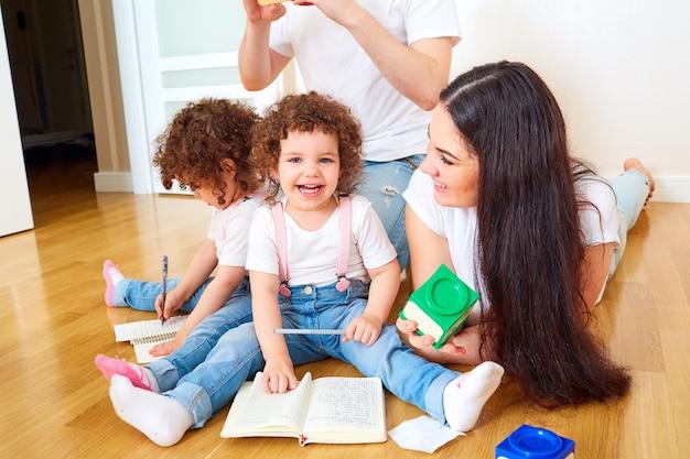 Famiglia felice che si diverte sul pavimento nella stanza mamma papà e figlia ragazza che ridono giocando a scrivere su un quaderno