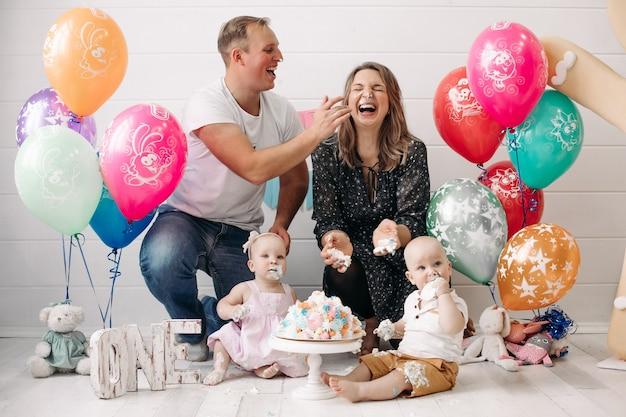 Famiglia felice che ha divertimento ottenere crema torta sporca sul viso che celebra colpo pieno di buon compleanno bambini. madre divertente e padre che ride godendo festa di anniversario di bambino circondato da decorazioni per le vacanze