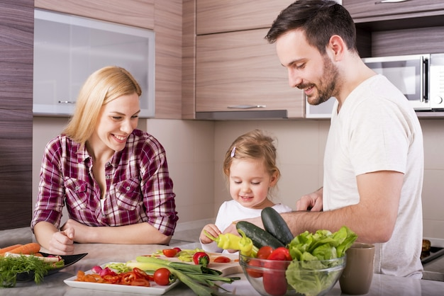 La famiglia felice si diverte in cucina mentre prepara l'insalata di verdure fresche
