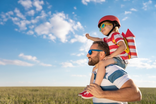 Famiglia felice che ha divertimento all'aperto. padre e figlio che giocano contro il fondo del cielo estivo blu.