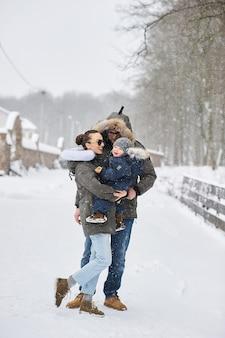 Famiglia felice che si diverte fuori vicino alla casa in inverno