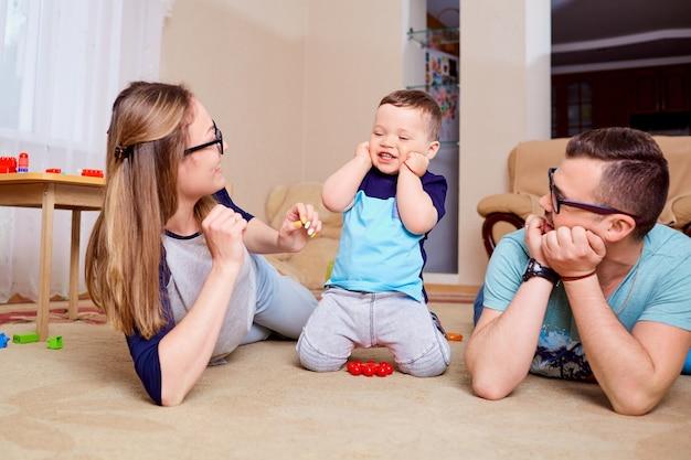 Famiglia felice che si diverte a giocare sul pavimento in camera