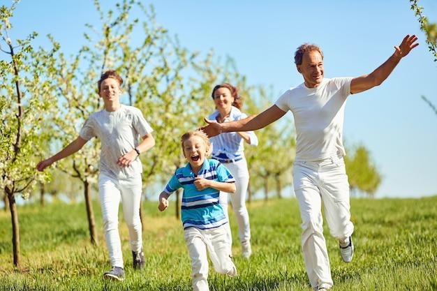 Famiglia felice che si diverte a passeggiare in giardino in primavera, estate