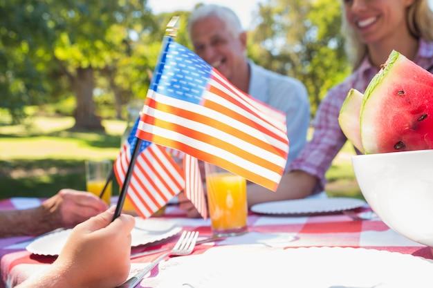 Famiglia felice che ha picnic e che tiene bandiera americana