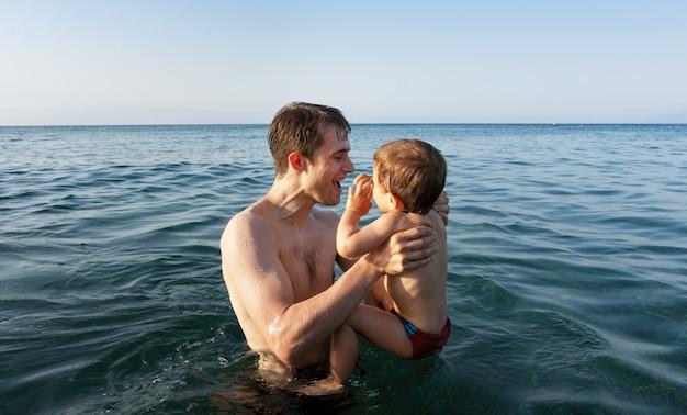 Famiglia felice e stile di vita sano. un giovane padre insegna a un bambino a nuotare nel mare