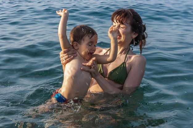 Famiglia felice e stile di vita sano. la giovane mamma insegna a un bambino a nuotare nel mare